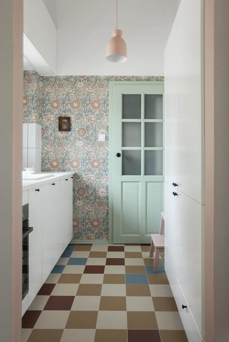 Il y a une petite cuisine avec du papier peint scandinave et des armoires blanches, des carreaux colorés au sol