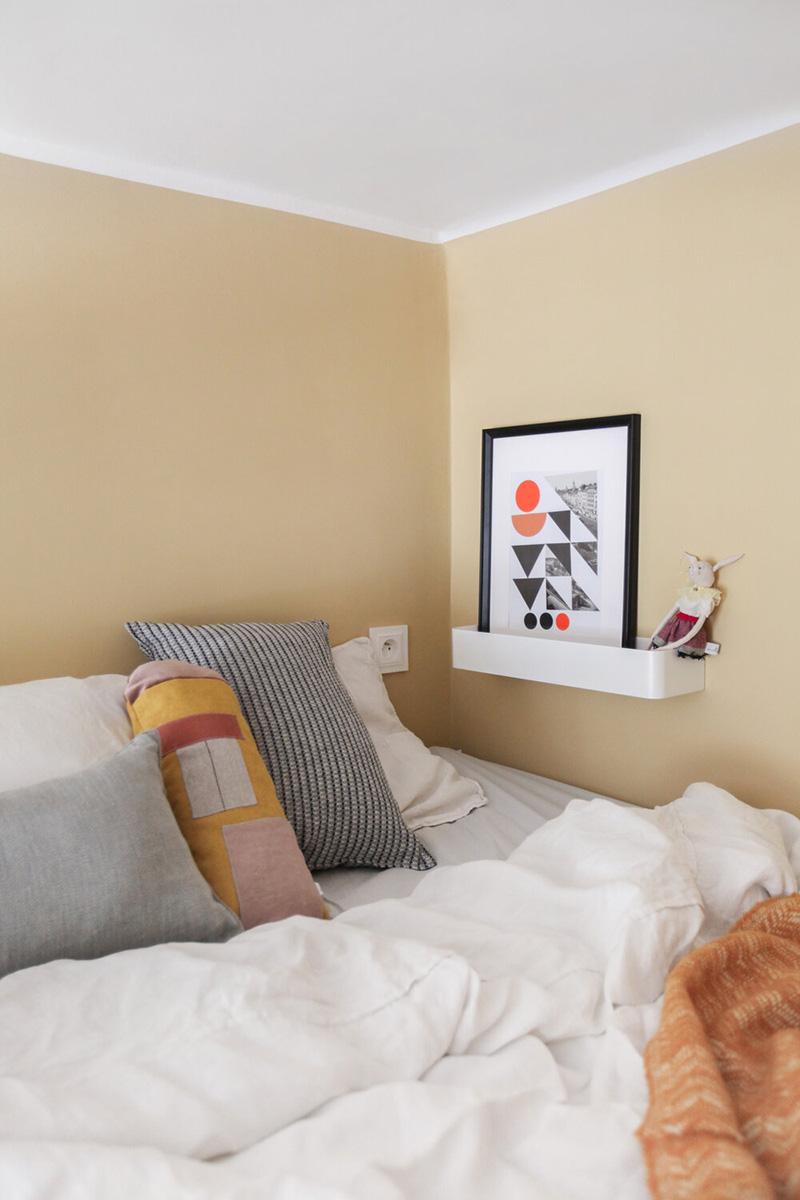 Une prise et un rebord avec une œuvre d'art rendent l'espace de couchage pratique et fonctionnel