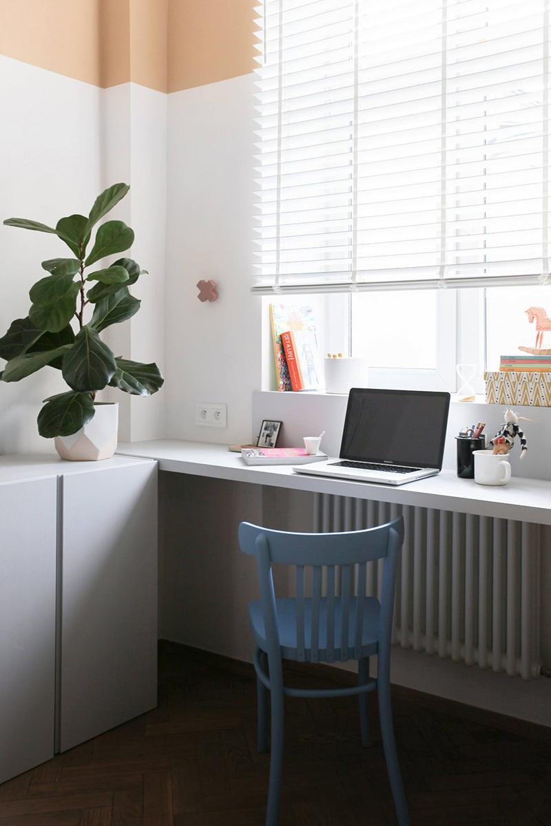 Les armoires blanches élégantes sont idéales pour le stockage, et un petit espace de travail est parfaitement accessoirisé pour être joli