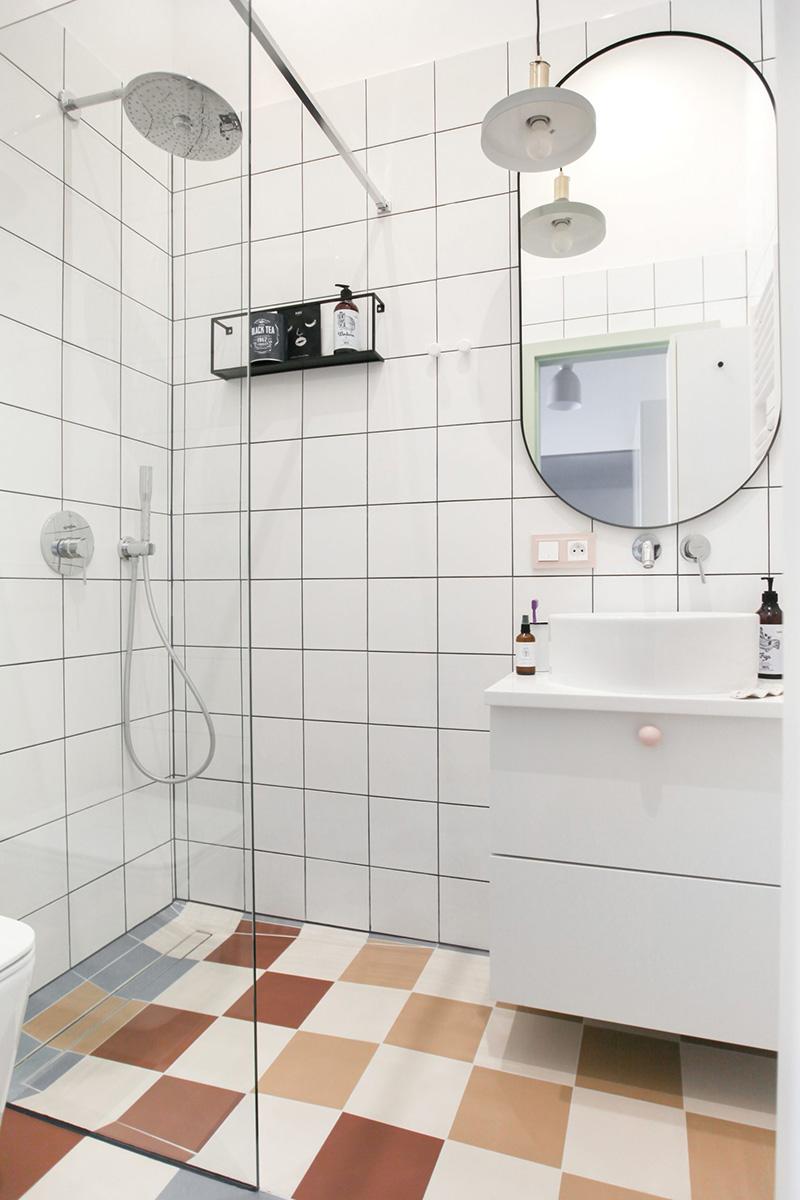 La salle de bain est revêtue de carreaux carrés blancs et de carreaux colorés au sol, et il y a tout le nécessaire ici