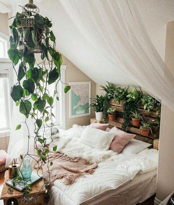 une chambre bohème mansardée avec un jardin de tête de lit en palette et une cage suspendue avec de la verdure est magnifique
