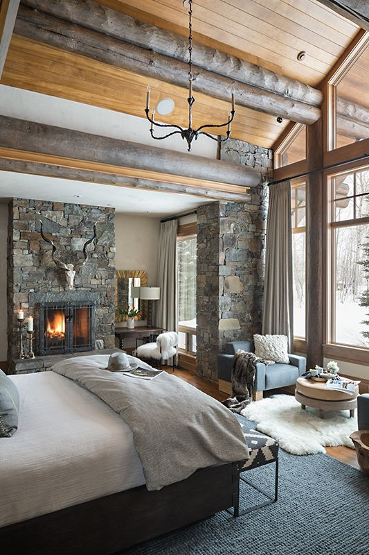 une chambre rustique avec des rondins de bois au plafond, un pilier revêtu de pierre et une cheminée en pierre
