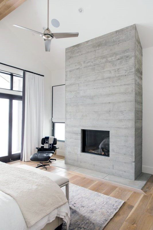 une chambre moderne aux tons neutres, avec beaucoup de lumière naturelle et une cheminée en béton qui donne à l'espace un look cool