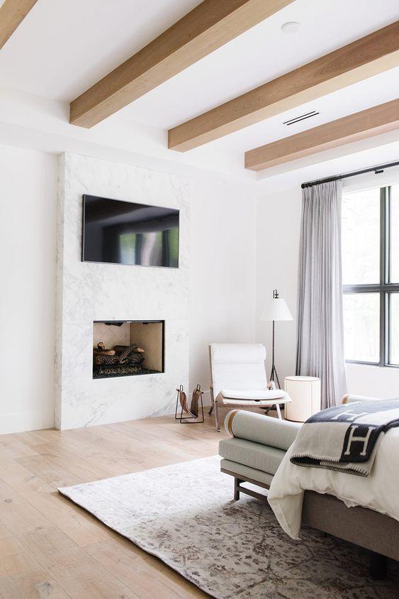 une chambre neutre moderne avec des poutres en bois élégantes, des meubles élégants, une télévision et une cheminée intégrée