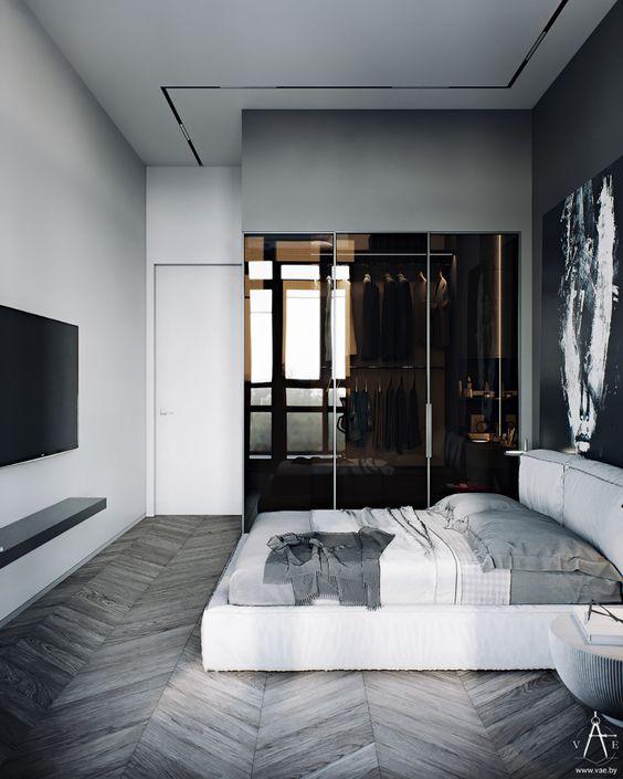 une chambre parentale minimaliste dont une partie occupée par un placard en verre marron est très chic et raffinée