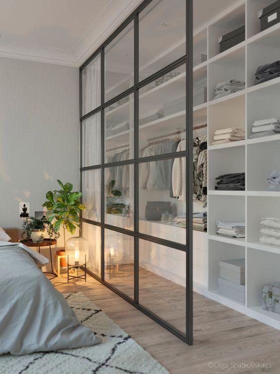 une chambre moderne et un placard séparés par un diviseur de porte-fenêtre ont l'air aéré et chic et disposent d'un espace de rangement ici
