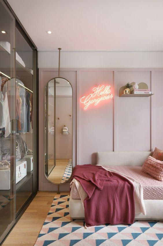 une chambre de jeune fille moderne et tendance en rose, avec des meubles élégants et un placard en verre avec des portes coulissantes