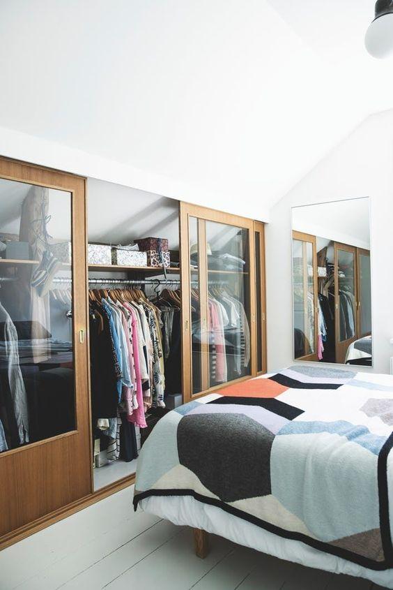 une petite chambre mansardée dans des tons neutres, avec sa partie maladroite recouverte de portes coulissantes en verre et servant de placard