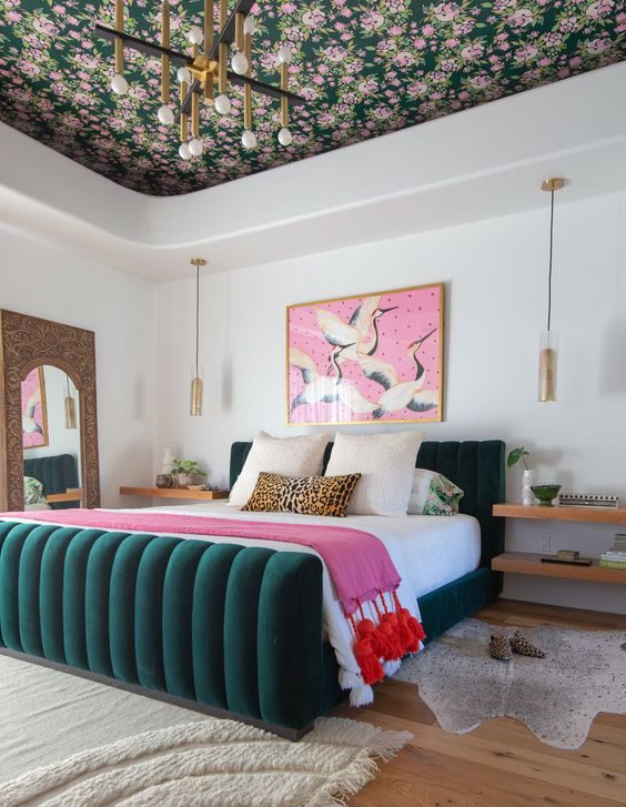 une chambre colorée moderne raffinée et chic avec un plafond fleuri, un lit vert chasseur et des touches roses c'est cool