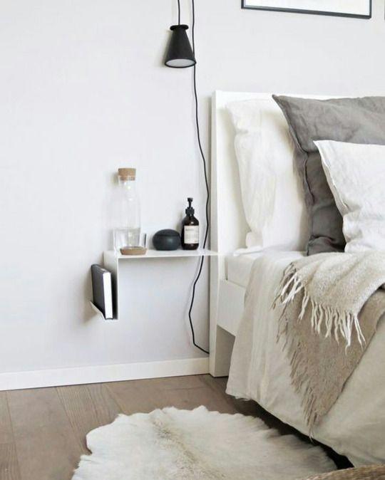 une table de chevet minimaliste accrocheuse en blanc, avec un livre rangé et quelques trucs sur le dessus est très aéré et cool