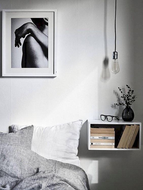 une chambre scandinave avec une table de chevet flottante ouverte avec des livres et une ampoule au-dessus de l'espace
