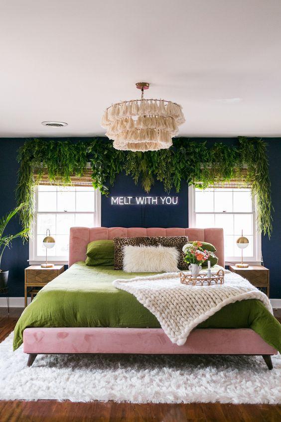 une chambre sarcelle à couper le souffle avec de la verdure suspendue, un lit rose et une literie verte et un lustre à pampilles