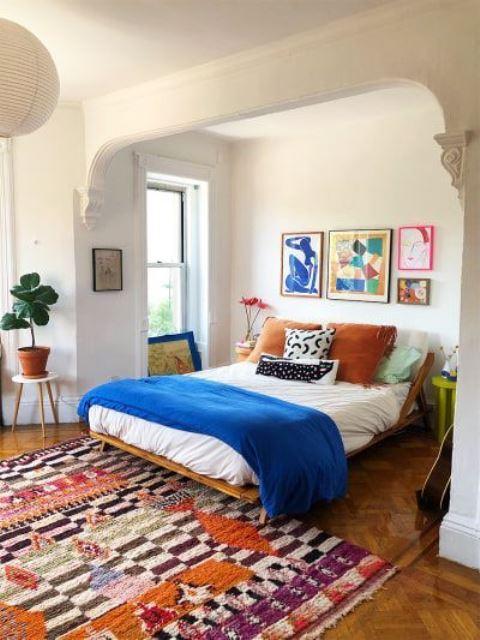 une chambre moderne et colorée avec un mur de galerie lumineux, une literie et des textiles audacieux et des plantes en pot