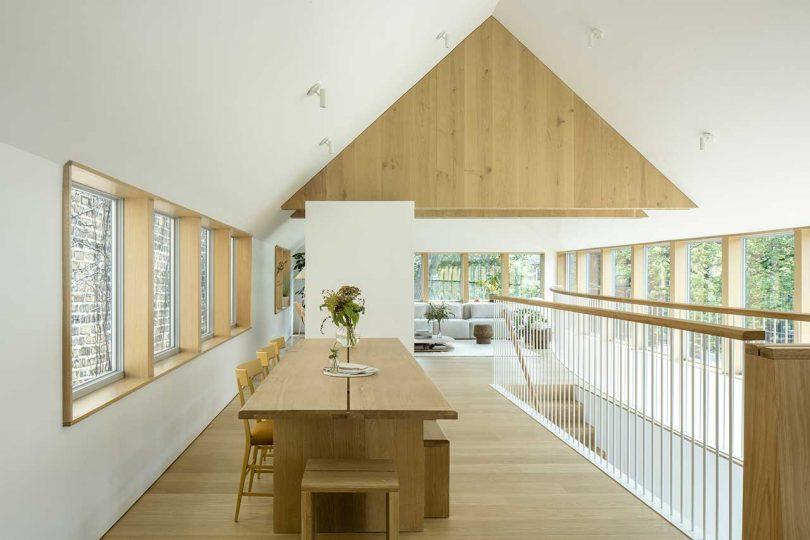 En haut des escaliers, vous pouvez voir une salle à manger avec une table et des bancs en bois et un salon près des fenêtres