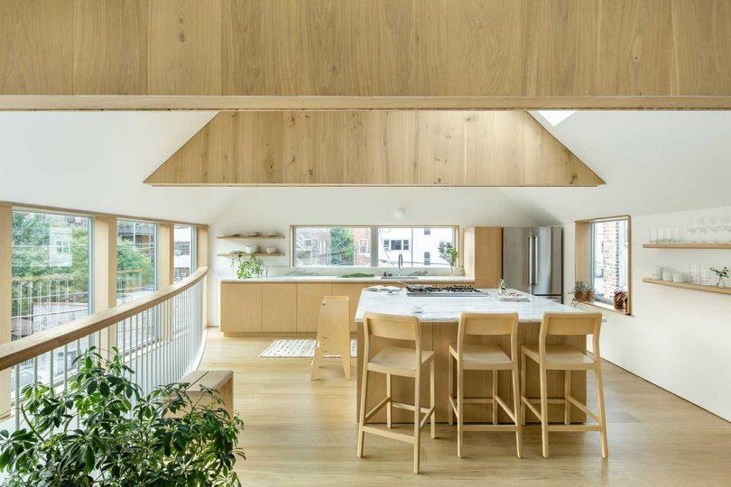 La cuisine est minimale, avec des armoires aux teintes claires avec des comptoirs en pierre blanche et un îlot de cuisine avec une zone de petit-déjeuner