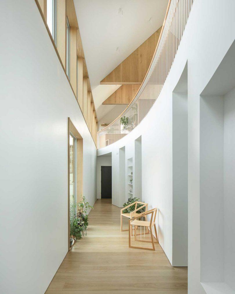 Il y a une balustrade incurvée et un petit couloir avec des espaces de rangement, des chaises et des plantes en pot