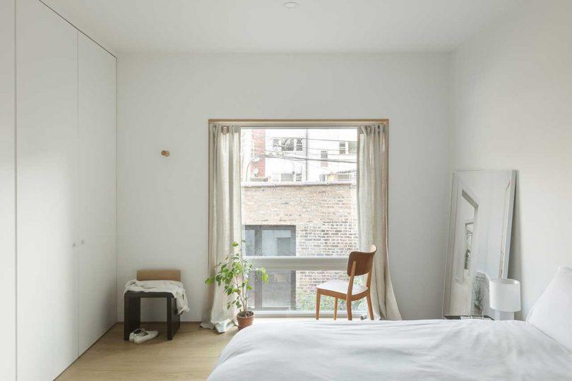 La chambre est décorée simplement, avec des armoires, un lit, des chaises et une fenêtre simple