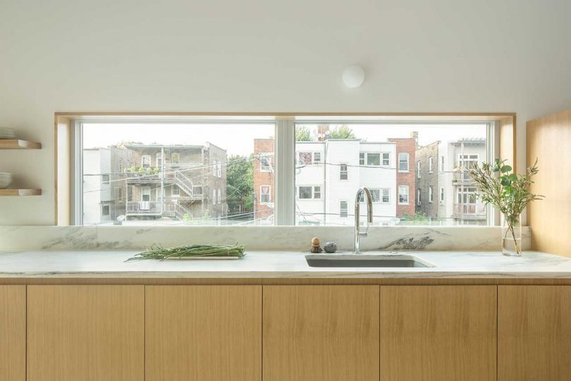 Un dosseret est remplacé par une fenêtre pour remplir la cuisine de lumière naturelle autant que possible