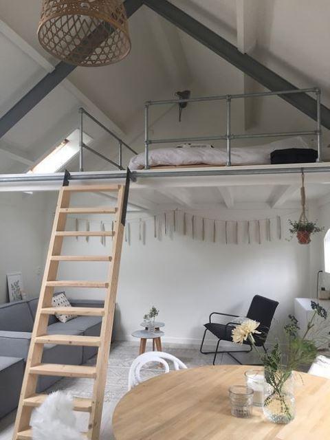 un appartement contemporain avec une chambre en mezzanine avec un puits de lumière et un lit plus une palette de couleurs scandinaves