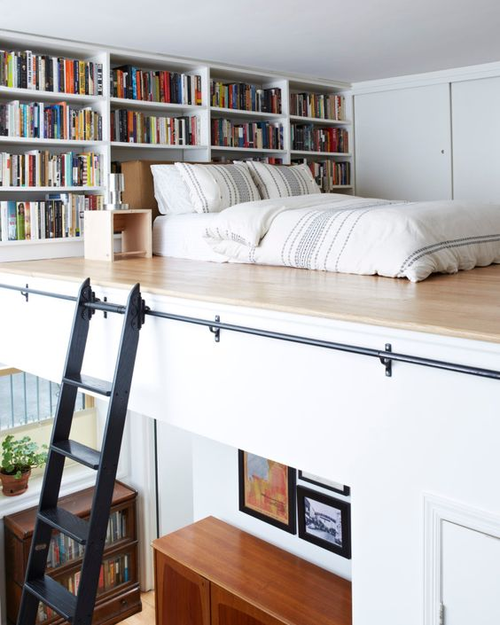 un appartement contemporain avec une chambre en mezzanine, des étagères intégrées et un matelas accroché au mur