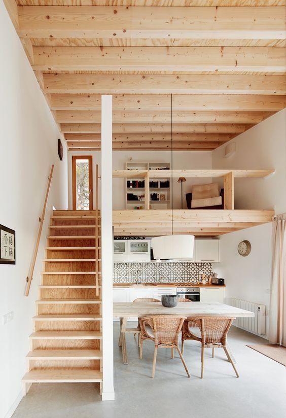 une maison contemporaine avec un plafond en bois et un escalier, avec une cuisine en bas et un espace lecture en mezzanine avec des étagères intégrées
