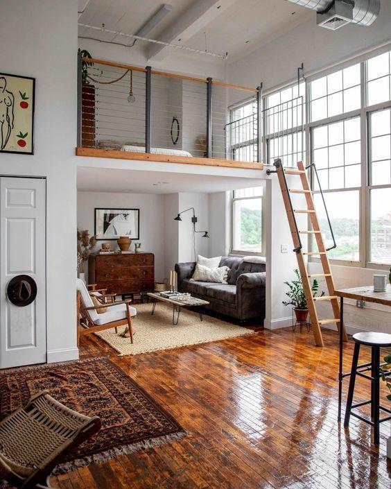 un espace moderne avec un salon avec une chambre en mezzanine au-dessus et des fenêtres à double hauteur pour remplir l'espace de lumière