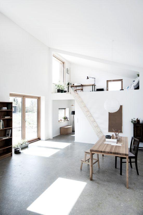 une maison spacieuse et minimaliste avec un espace de travail en mezzanine, de la verdure en pot et une salle à manger en bas des escaliers