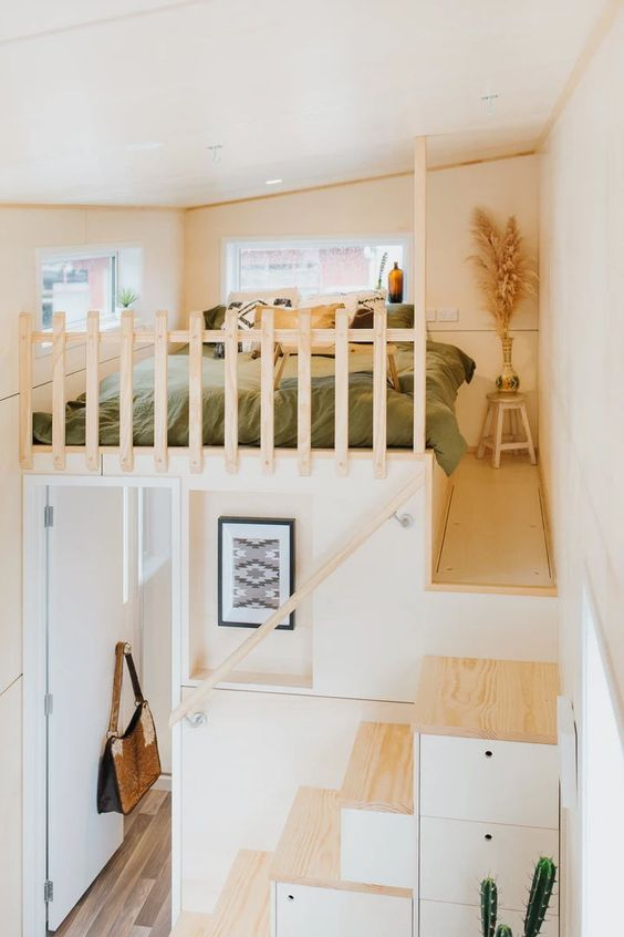 un petit appartement bohème neutre avec une chambre en mezzanine et un escalier composé de petits tiroirs de rangement