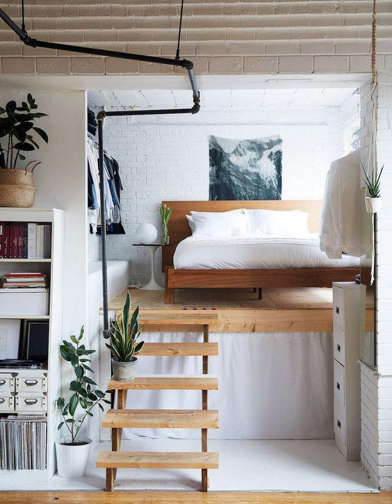 une petite et chic chambre loft moderne avec un lit en bois, un placard ouvert et une œuvre d'art cool est une idée audacieuse