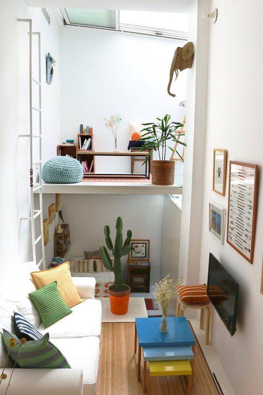 un petit appartement coloré avec un salon, une chambre en bas et un espace de travail en mezzanine avec une lucarne au-dessus est amusant