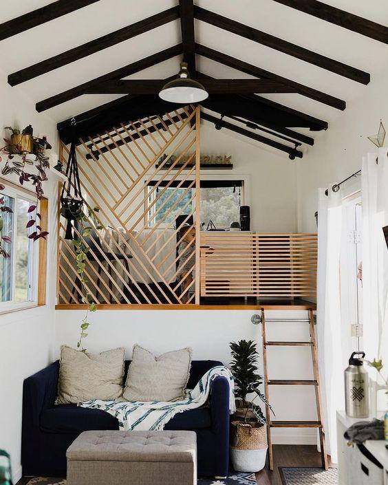 une petite maison contrastée avec un salon et une chambre en haut des escaliers, avec des paravents en bois pour couvrir l'espace