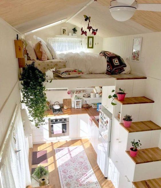 une petite maison avec une chambre en mezzanine et un escalier de rangement plus une cuisine en bas contient tout ce dont vous pourriez avoir besoin pour vivre