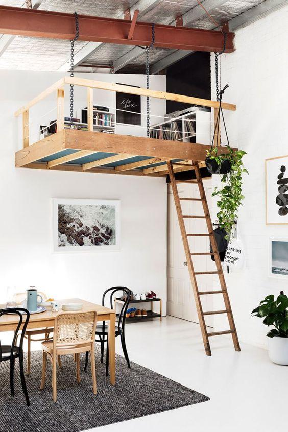 un appartement éclectique avec une touche scandinave et un espace de lecture et de travail loft avec des étagères est très cool