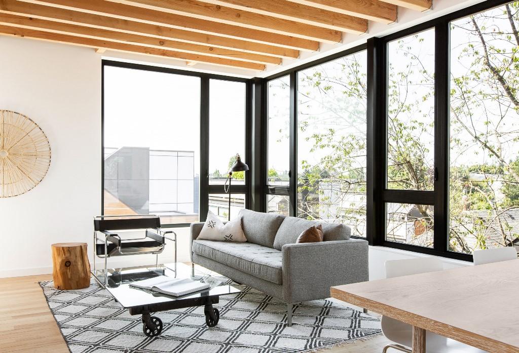 Le salon est aménagé avec des meubles confortables, une table à roulettes et un tapis imprimé