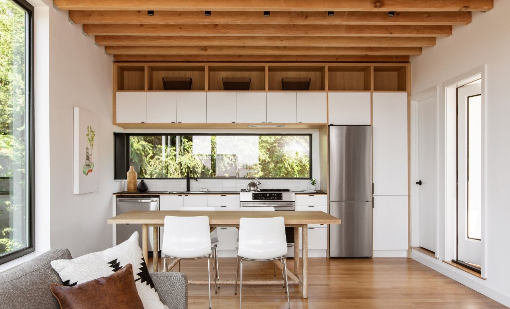 La disposition ouverte montre une cuisine, une salle à manger et un salon, il y a beaucoup de lumière naturelle et une sensation aérée