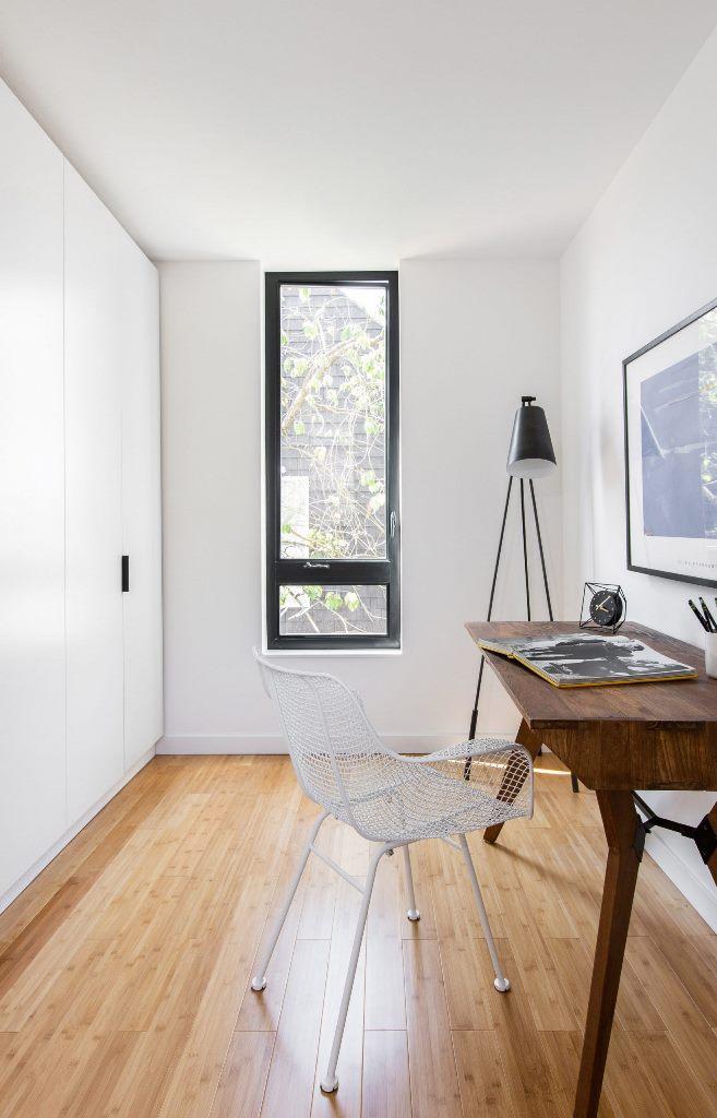 L'espace de travail est aménagé avec des armoires épurées, un bureau vintage et une chaise en métal
