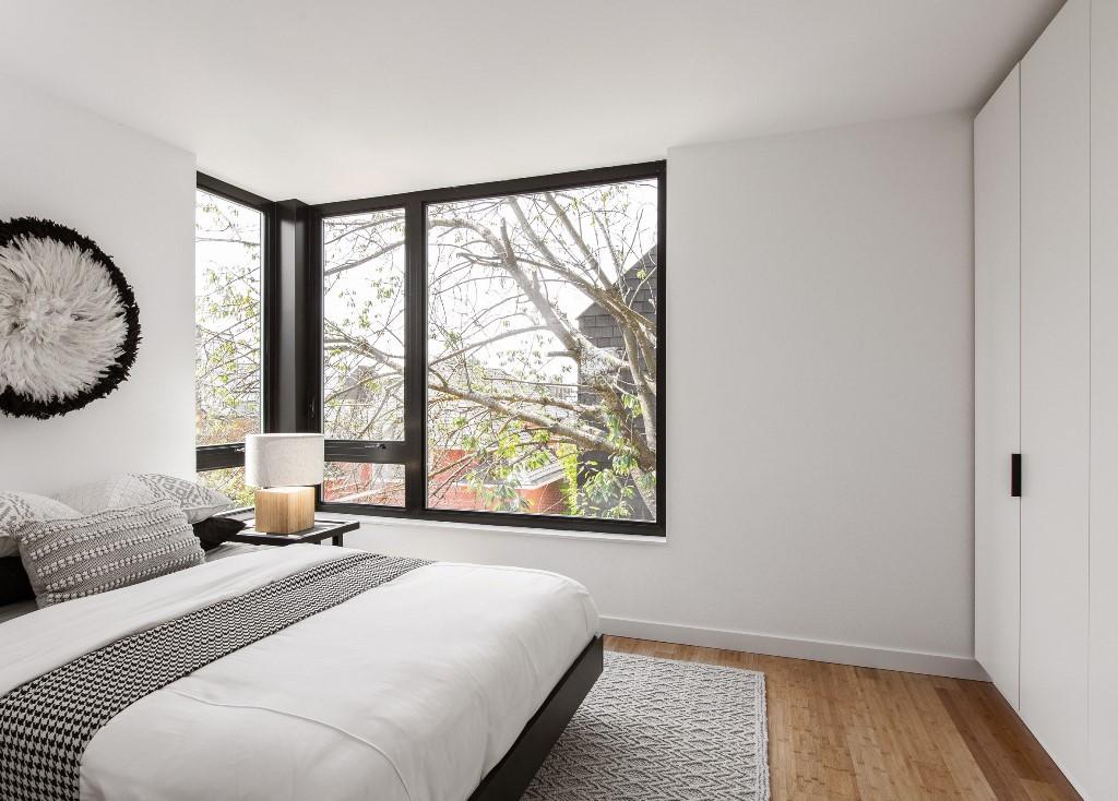 La chambre est faite dans une palette de couleurs monochromes, des textiles imprimés et une jolie œuvre d'art