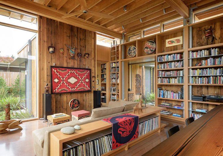 Le salon est aménagé avec des étagères ouvertes, un grand sectionnel, un art bohème lumineux et des accessoires