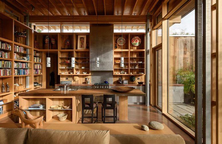 La cuisine est aménagée avec beaucoup d'étagères ouvertes et un grand îlot de cuisine en bois avec un endroit pour les repas