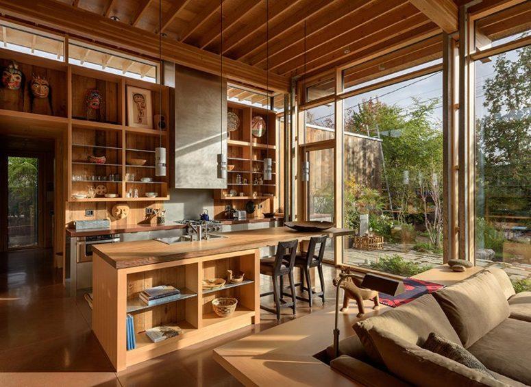 L'agencement principal comprend une cuisine, un salon et une salle à manger et est baigné de lumière naturelle à travers les murs vitrés