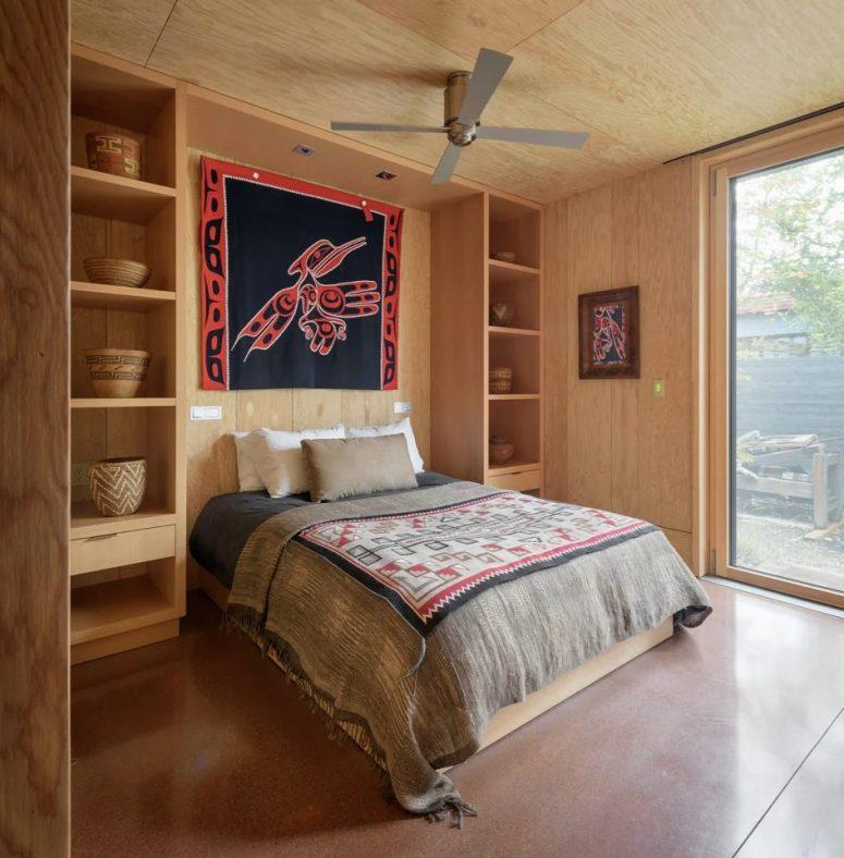 La deuxième chambre est aménagée dans le même style que la première, avec des étagères ouvertes et des textiles bohèmes lumineux
