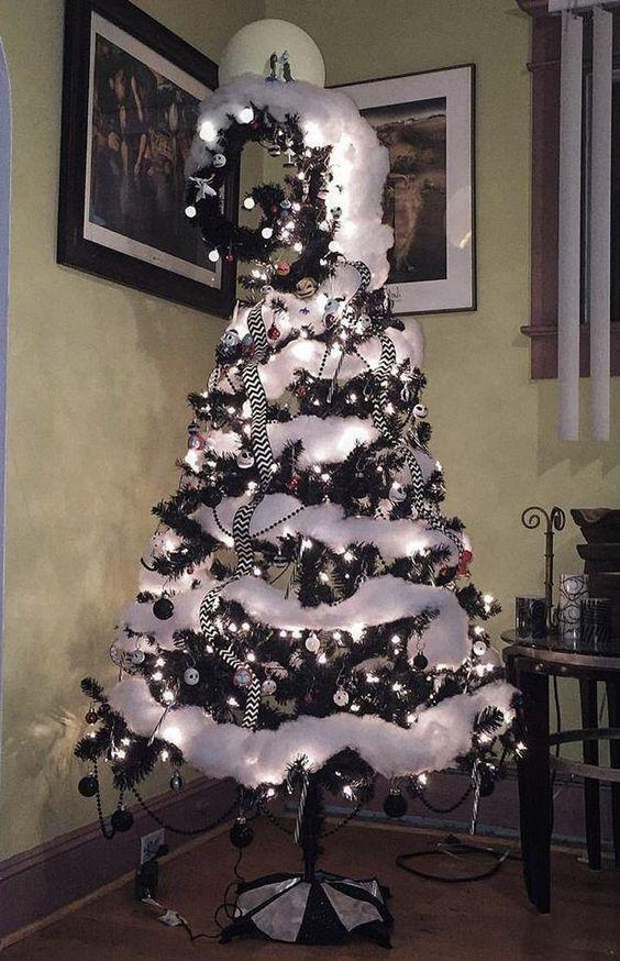un sapin de Noël noir avec des ornements en noir et blanc, de la neige en coton blanc, un haut en spirale et des rubans à rayures