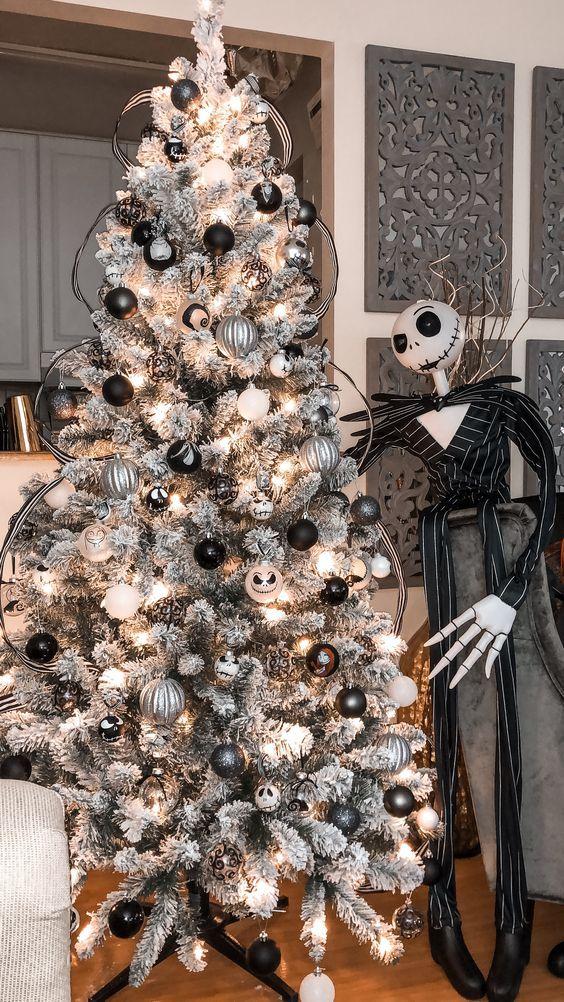 un magnifique sapin de Noël gris avec des ornements blancs, noirs et argentés, ceux de Jack Skellington et sa silhouette à côté de l'arbre