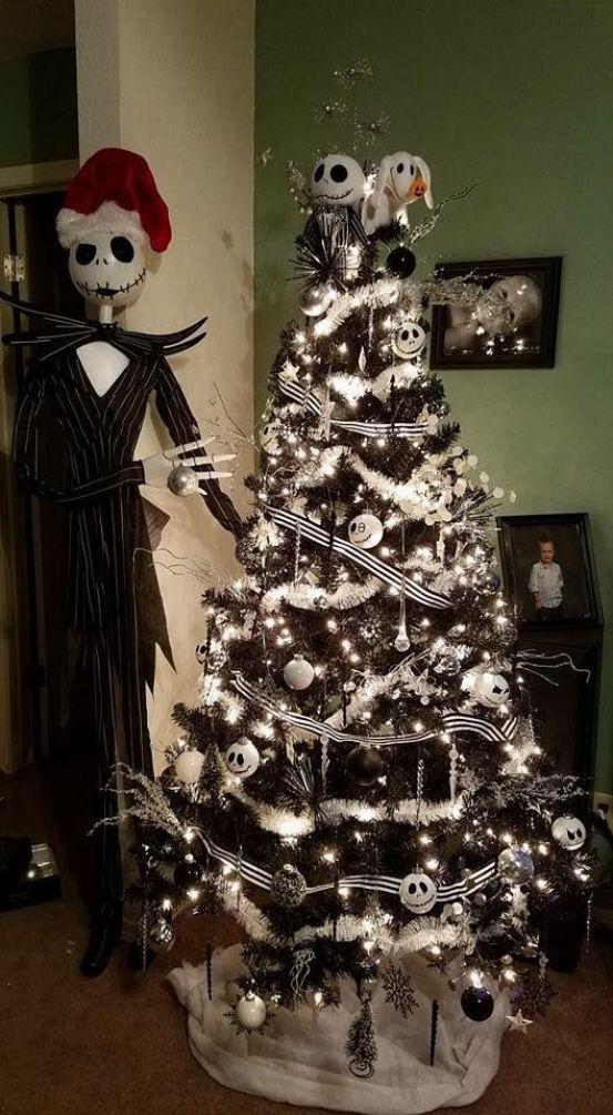 un sapin de Noël noir avec des rubans noirs et blancs, des guirlandes blanches, des lumières et des ornements Skellington noirs et blancs plus Jack Skellington à côté