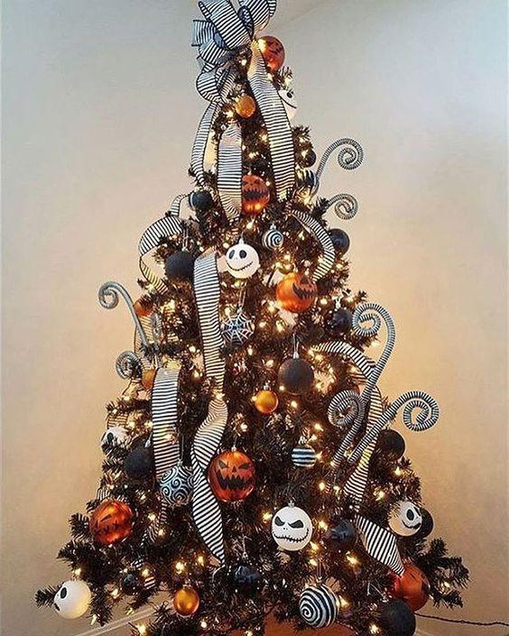 un sapin de Noël noir avec des lumières, des ornements orange, noir et blanc et ceux de Jack Skellington, des rubans rayés et des boucles