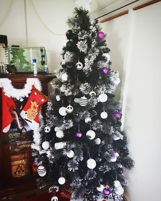un bel arbre de Noël noir floqué avec des ornements blancs et violets ainsi que ceux de Jack Skellington est une idée lumineuse et contrastée à rock