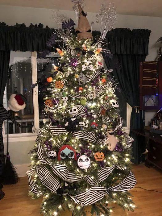 un arbre de Noël avec des lumières, des ornements Nightmare Before Christmas, des rubans rayés, des branches et des brindilles brillantes et un chapeau sur le dessus