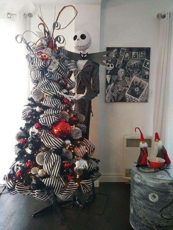 un sapin de Noël noir avec des rubans rayés, des ornements en or, argent, rouge et noir et une figurine de Jack Skellington à côté