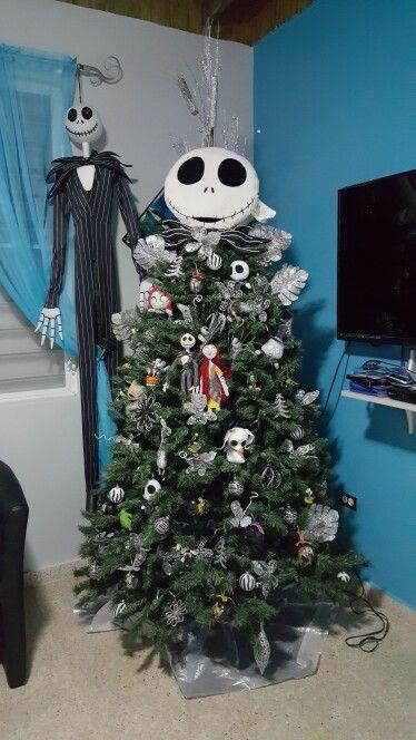 un arbre de Noël décoré d'ornements Nightmare Before Christmas et avec Jack Skellington debout à côté de lui