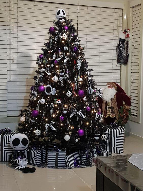 un arbre d'Halloween noir décoré de lumières, d'ornements Jack Skellington, de violets et de quelques nœuds à rayures